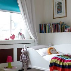 White-painted furniture and white walls bounce light around this small bedroom. Splashes of bright colour and a cosy throw create a vibrant look.