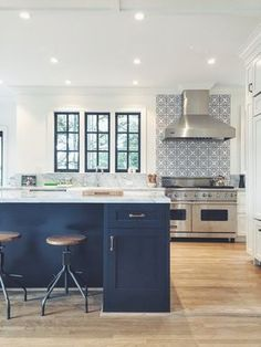 Kitchen with navy blue island, white walls, black framed windows and patterned cement tile backsplash.