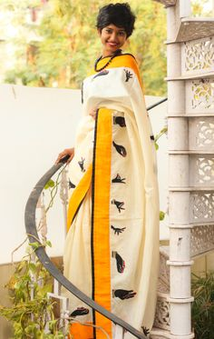 Off white saree with yellow and black border and Indian classical mudras.