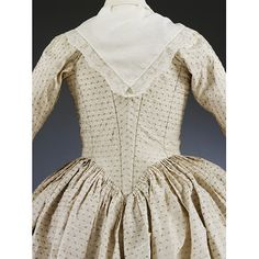 Gown      Place of origin:      Spitalfields, England (textile, weaving)     London, England (ensemble, sewing)     Date:      1775 - 1780 (weaving)     1779 (sewing)     28/09/1779 (worn)     1870 - 1910 (altered)     Artist/Maker:      Unknown (production)     Materials and Techniques:      Silk, linen, silk thread, linen thread, silver thread, silver spangles, silver strip, whalebone; hand woven textile and fringe, hand sewn