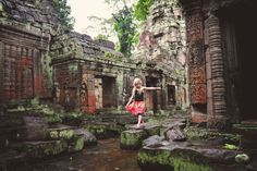 Young girl playing on the stones of an ancient temple in Cambodia