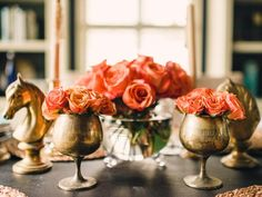 Use Unexpected Objects When it comes to centerpiece ensembles with eclectic style, consider using unexpected vases and candleholders. Here, vintage brass goblets were used to hold orange roses. A grouping of brass horse busts in the same finish adds flair.