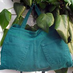 Denim side of the bag with decorative green leaves