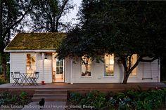 So geht zu Hause: warmes Licht erleuchtet das mossbedeckte Tiny House, ein Kätzchen huscht durch den Garten. Die Holzveranda wurde kurzerhand um einen angrenzenden Baum herumgebaut.