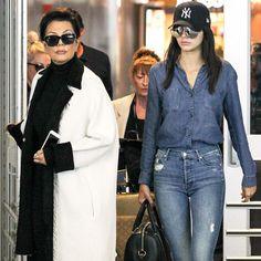 Kendall Jenner usa look total denim, com camisa jeans e calça jeans. Super sporty, enquanto sua mãe Kris Jenner arrasa em um maxi coat preto e branco.