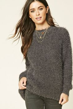 A knit sweater featuring a ribbed crew neckline, dropped long sleeves, and a loose fit.