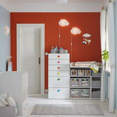 A children's room with a white changing table filled with grey boxes for diapers and clothes. Shown together with a storage combination with white drawers and colourful knobs.