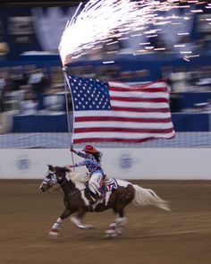 Fireworks and the American flag carried by a Catalena Cowgirl during the opening ceremonies of the Pin Oak Charity Horse Show