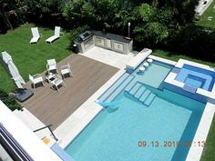 Swimming pool with swim-up bar (connected to outdoor kitchen) hot tub at luxury home in Biscayne, Florida