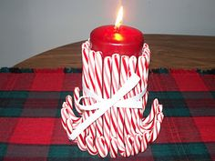 Use tall white pillar candle and red ribbon.  Put sticky pads around the candle ~ stick candy canes on, tie ribbon around. Pretty centerpiece!