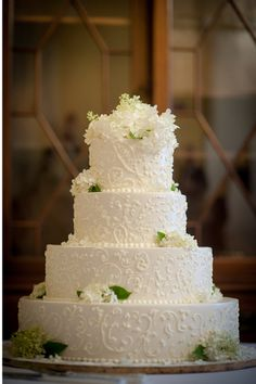 White Wedding Cake with White Flowers and Green Leaves
