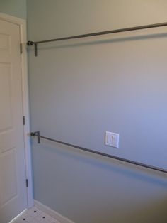"""Use stacked curtain rods in laundry room to hang dry clothes or to air dry wet clothes."" Genius."