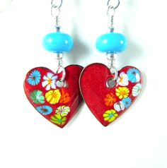 Handmade colorful heart enameled copper and glass dangle earrings featuring red, yellow, white, orange and turquoise blue enamel charms; turquoise blue SRA artisan crafted lampwork beads; and sterling silver.  These beautiful earrings are composed of 18 mm enameled copper hearts and artisan crafted glass beads. I made the enamel charms by fusing layers of powered glass to copper hearts with my torch. The hearts are red with yellow, blue, orange and white flowers. The lampwork beads are…