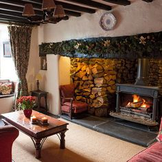 In this Welsh farmhouse, a dainty window seat is framed by thick floral curtains in the living room, where warm fabrics and colors add to the period style.  A cosy wood burner sits in an imposing fireplace adding to its rustic country charm.