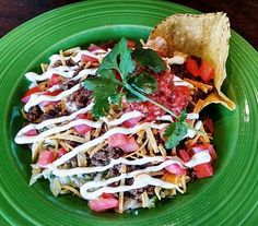 Taco salad with crisp tortilla strips, seasoned ground beef, shredded iceberg lettuce, Tillamook cheese, white onions, diced tomato, cilantro, lime sour cream and topped with chipotle ranch dressing. #tacosalad #SPORT