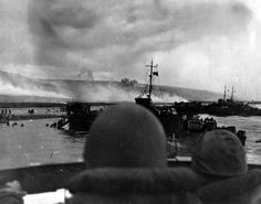 USS LCI(L)-553 and USS LCI(L)-410 land troops on Omaha Beach during the initial assault. Photographed from the conning station of another LCI(L). LCI(L)-553, hit by two shells, was left after D-Day