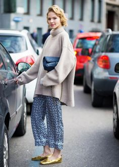 Beige oversized roll-neck worn with printed pajama pants, gold ballet pumps and a black Chanel bag.