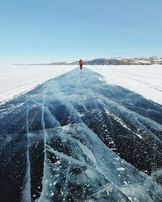 In the clear   In winter, the ice covering Lake Baikal can be up to 1.5 metres thick, and the lake serves as a temporary road for trucks travelling across it. The experience of driving on the lake is pretty impressive – and also illegal, except for the road to Olkhon Island.   In this image a lone figure walks away from the camera on a bright sunny day and along and over the aforementioned lake in Siberia.