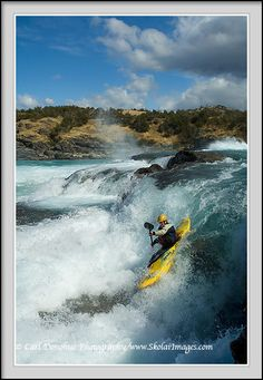 Clas 5 whitewater kayaker drops down a Class 5 rapid on the Baker River, patagonia, Chile.