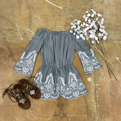 You will love this sage green romper! It sits off the shoulders and has an elastic top to give the perfect fit. The sleeves are long and are adorned with an off-white, embroidered design. The waist ti