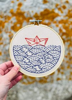 """Hook Line & Tinker creator Laurie Dolhan writes, """"I have great admiration for the beautiful simplicity of Japanese design, and Hope Floats My Boat is my own playful interpretation and nod to the aesthetic. The pattern was created from my own original, hand-sketched illustration. A red origami boat on a sashiko inspired sea, this modern design is all about texture and contrast and is made using the simplest of stitches.""""Your friends and family will undoubtedly be very impressed by your finish Creative Embroidery, Simple Embroidery, Modern Embroidery, Embroidery Hoop Art, Hand Embroidery Patterns, Embroidery Stitches, Broderie Simple, Diy Broderie, Design Japonais"""