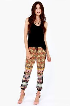 "One part cosmopolitan, and one part psychedelic chic, the Retro-politan Yellow Print Harem Pants are as exciting as the buzz of the big city! Sharpen up your street style in these silky woven pants that have a pale yellow and multicolored print trimmed in black along the sides, waist, and elastic ankle cuffs. Elastic waistband includes a decorative drawstring at front. Unlined. Model is 5'10"" and is wearing a size small. 100% Polyester. Hand Wash Cold. Imported."
