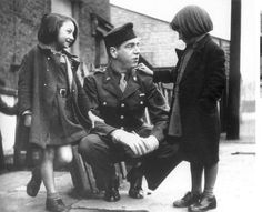 """American officer with English war orphans who had been """"adopted"""" by his unit.  (London, 1943)"""