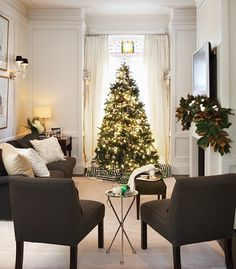 Elegant striped wrapping paper on the presents add a jaunty, tailored note to an old-world style Christmas tree. A magnolia-leaf garland, decorated with simple white ornaments and pine cones, adorns the mantle.