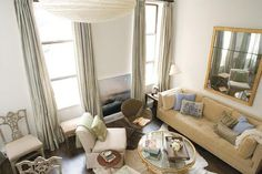 Living room-  camel blue seafoam green modern living room design with soft sand paint wall color, beige tufted modern sofa, gray silk drapes, rice paper light pendant, oval brass French coffee table, ivory linen slipper chairs, French accent chairs, gilt mirror, blue ivory beige silk throw pillows, ivory cowhide rug and espresso stained wood floors.