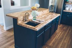Jess Ann Kirby's kitchen renovation with Lowes. New butcher block countertops with delta faucet and dark green chalk painted cabinets