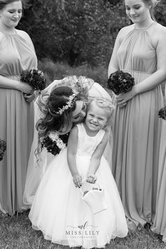 Bride kissing her flower girl in black and white by Miss Lily Photography. Central Michigan wedding photographer.