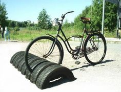 Tires were half-buried in the ground to make this clever and convenient recycled bike stand. With this simple solution, the bicycle's tire could be locked to the tire in the ground to secure it. #earthday