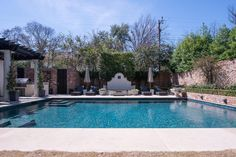 A sparkling blue swimming pool sits amidst brick walls like a secret oasis.