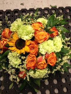 Dekorasjon med gul solsikke oransje roser og lyse grønne nelikker