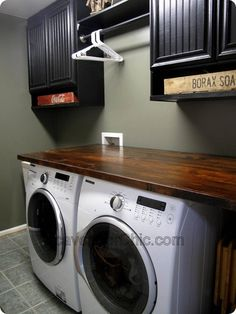 Love the large countertop and hanger space in this laundry room