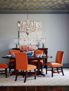 Orange chairs seem perfectly at home in this beach style dining room [Design: Andrew Howard Interior Design]