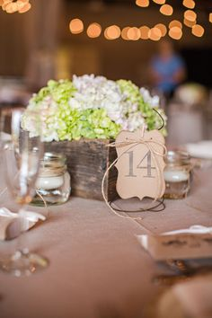 barn wedding reception table..center pieces are old barn wood flower boxes..small mason jars with floating candles..rusty bed coils hold the table numbers