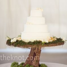 The simple white cake was set on a handmade wooden stand and surrounded by flowers and moss for a stunning, rustic display.