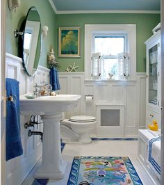 """This """"sanitary"""" white bathroom designed by Carisa Mahnken edges toward cottage style with a wood wainscot, extra color, and a  whimsical wave border in the tile floor."""