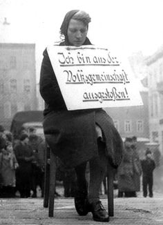 """A German woman faces public humiliation because of a romantic affair with a Polish man. German racial laws were strictly enforced and sexual relationships betweenGermans and Slavs were illegal. The placard around her neck reads, """"Ich bin aus der Volksgemeinschaft ausgestoßen!""""(""""I am Expelled from the People's Community!"""")Altenburg, Thuringia, Germany.7 February 1942."""