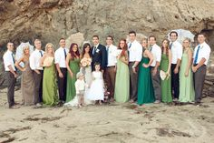 Christine Bentley Photography beach waves bridal party different shades of green Bari jay dresses maxi full length groomsmen brown navy suit lace parasols