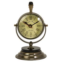 Brass table clock with a Roman numeral face and pedestal stand.   Product: Table clockConstruction Material: Al...