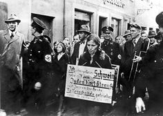 """SS men leading a woman through the streets. Hanging from her neck is a sign that reads: """"I am swine. I slept with the Jew Karl Strauss and thus polluted the German race""""."""
