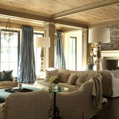 Living room with wood plank ceiling, linen furniture covers, grey stone and blue silk curtains. Home Living Room, Living Room Designs, Living Spaces, Small Living, Tostadas, Family Room Design, Family Rooms, Living Furniture, Furniture Board