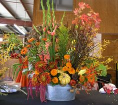 A large and abundant selection of vibrant fall colors.  Pumpkins, fall leaves and lots of vines and draping flowers in a rustic galvanize large tin pail.