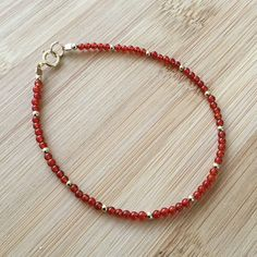 "A narrow bracelet of brilliant red carnelian, interspersed with 14K gold filled beads, is perfect for layering. It also makes a slender, elegant statement when worn alone. The bracelet is 7"" long and fastens with a gold filled spring clasp. The 2mm beads are quite small, giving"