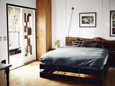 """studio home with 580 square feet in Los Angeles, California, USA (""""For the headboard, Roberts fastened a huge slab of redwood to the wall but put it on hinges so that, when the bed is raised, the piece of wood can flip down to double as a desk."""")"""