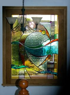 """Abstract stairwell panel in oak opening light. 37"""" x 52"""", September 2008. Made with English Antique glasses and Spectrum waterglass, detailed with traditional painting."""