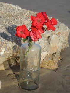 Flores en botellas de cristal como decoración para tu boda