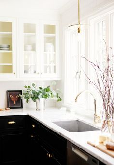 Brass pendant over a kitchen sink Mix of finishes, dark lower cabinet with white uppers. brass accents and marble.